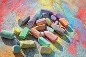 a collection of used colorful sidewalk chalk is laying on a rainbow swirl artwork drawn on the pavement poster