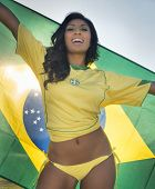 Beautiful happy smiling young woman holding Brazil flag wearing soccer top and bikini bottom poster