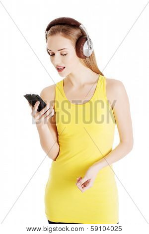 Beautiful casual woman in yellow top is listening to music. Isolated on white.