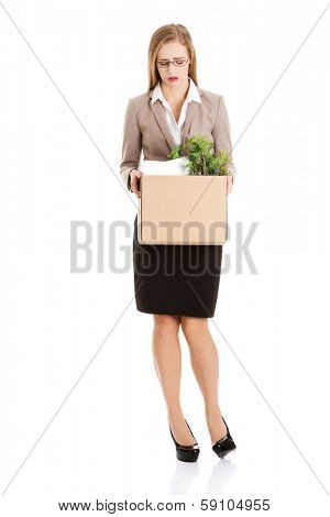Beautiful caucasian business woman is sad because she was fired from work and is holding box with her personal things. Isolated on white.