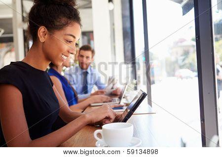 Businesswoman Using Digital Tablet In Coffee Shop