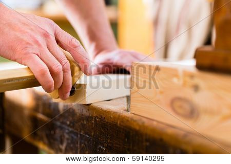 Carpenter working on wooden workpiece in his workshop or carpentry