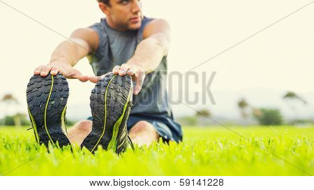 Attractive fit young man stretching before exercise, sunrise early morning backlit. Shallow depth of field, focus on shoes