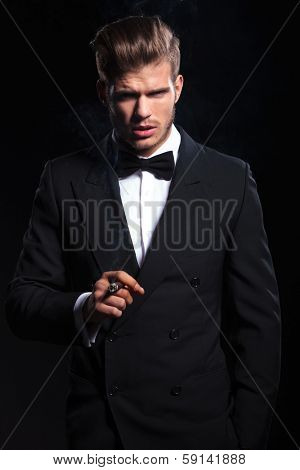 dramatic picture of an elegant man smoking a cigar on dark background