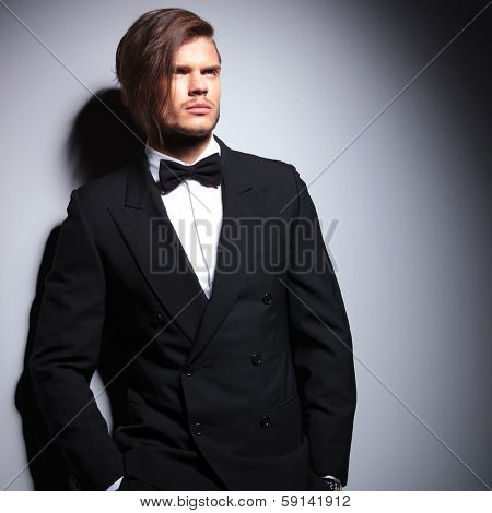 relaxed young fashion model in suit with bow tie looking away against gray studio background