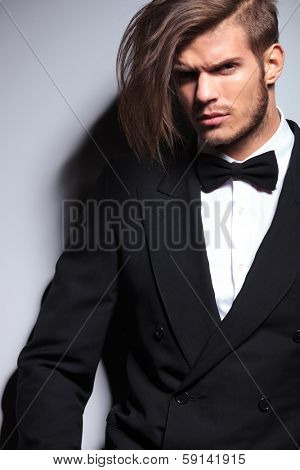 cutout picture of an elegant young fashion man with long hair in tuxedo  looking at the camera.on gray background