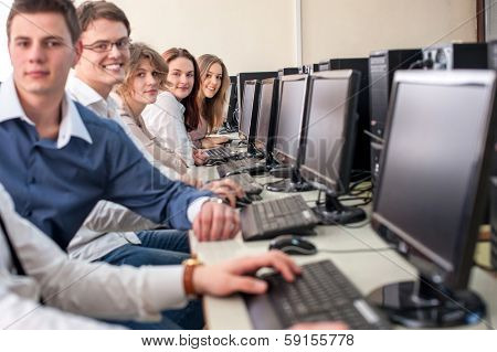 Smiling students sitting by computers in schoolroom