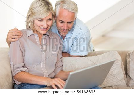 Portrait of a happy mature couple using laptop on sofa at home