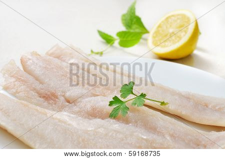 closeup of a plate with some raw pollack fillets
