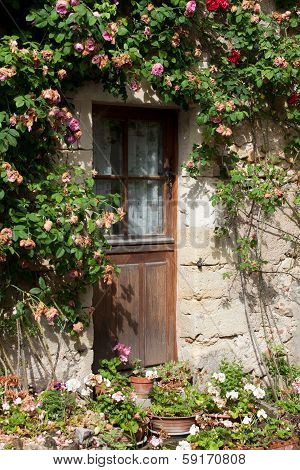 old cottage with roses around  the door