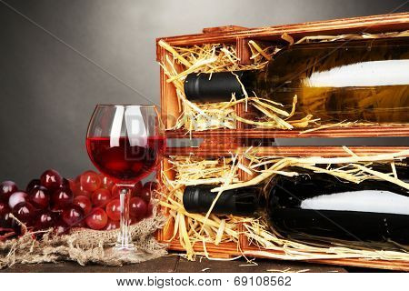 Wooden case with wine bottles, wineglass and grape on grey background