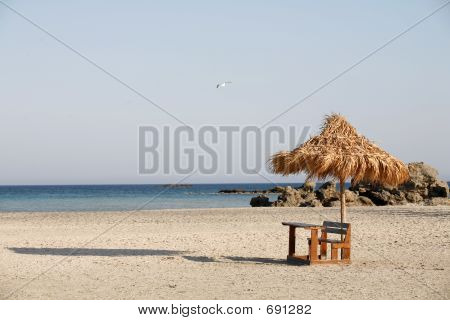 A desk and thatched umbrella sit inconguously on Elafonissos beach, Crete. An ideal place for doing holiday homework or catching up on your backlog at work, scrutinised by a passing seagull. poster