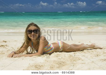 Young Girl Laying Down On White Sandy Beach..
