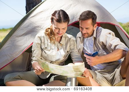 Outdoorsy couple looking at the map outside tent on a sunny day