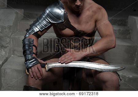 Gladiator in armour sitting on steps of ancient temple looking a