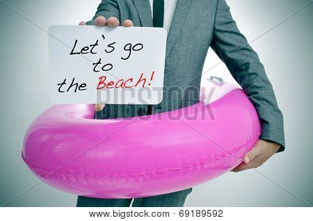 businessman with a pink swim ring showing a signboard with the text let's go to the beach written in it