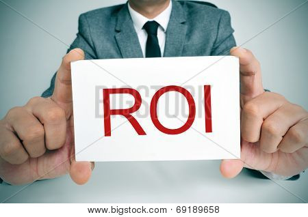 businessman sitting in a desk showing a signboard with the text ROI, ROI, acronym for Rate of Interest or Return on Investment, written in it