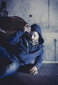 urban scene of young alcoholic grunge man sitting on ground street corner drinking alcohol bottle with shadow on concrete wall in edgy lighting at night in the city poster
