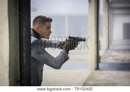 Well dressed handsome young detective or policeman or mobster holding a gun