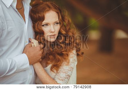 A young man and a red haired woman in the summer in the Park.