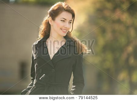 golden lady looking down in trench coat autumn time