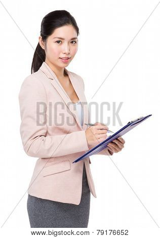 Businesswoman jot some note on clipboard