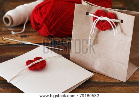 Saint Valentine decoration: handmade crochet red heart for greetings card and gift package. Selective focus poster