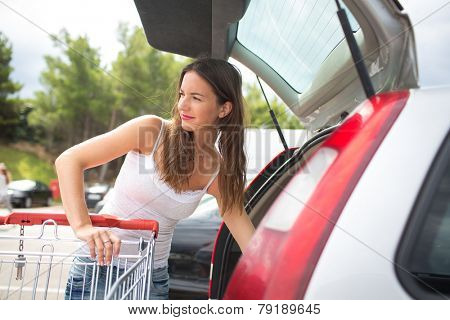 Beautiful young woman shopping in a grocery store/supermarket (color toned image), putting the groceries into her car in the parking lot, looking around