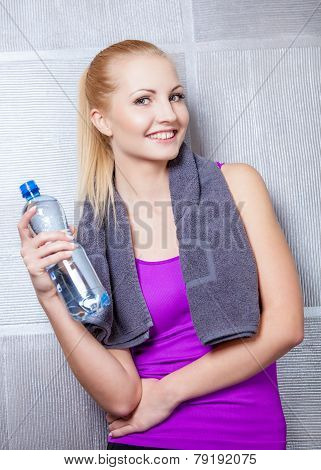 Pretty blonde woman smiling after fitness training drinking water