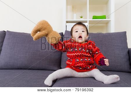 Asian little girl playing doll bear on sofa