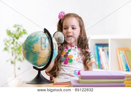 child reading with magnifying glass look the globe