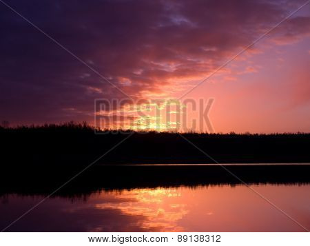 Clouds at sunrise over the forest lake reflected in the water