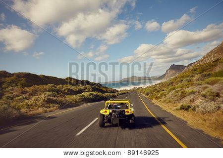 Couple Driving In Small Car On Open Road