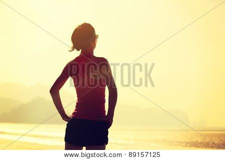 young fitness woman runner on sunrise seaside