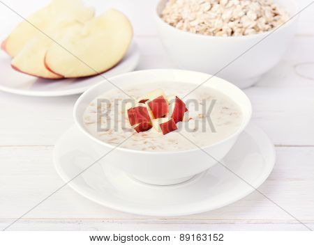 Oatmeal porridge with red apple slices on white wooden table poster