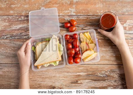 healthy eating, storage, dieting and people concept - close up of woman hands with food in plastic container at home kitchen