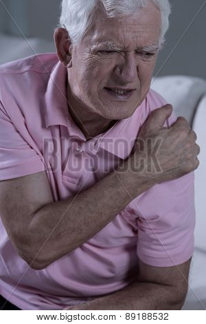 Aged sad grandfather with painful shoulder joint poster