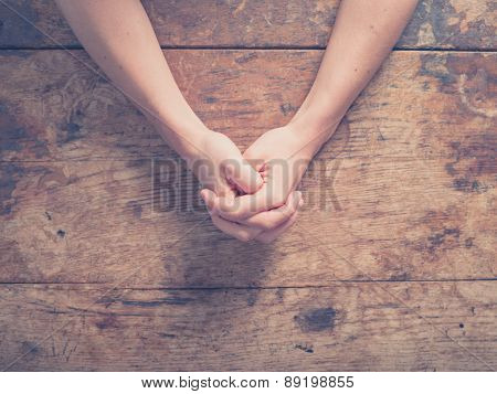 Female Hands Folded At Table