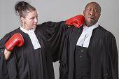 caucasian woman wearing a lawyer toga punching a black man wearing a lawyer toga poster