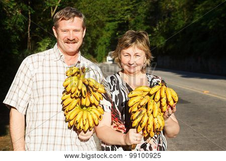 Couple Man And Woman Smiling And Holding Butch Of Bananas