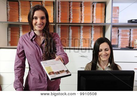 Women Handing Over Dvd At The Video Rental Store
