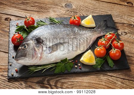 Fresh Fish With Tomato And Lemon On Old Table