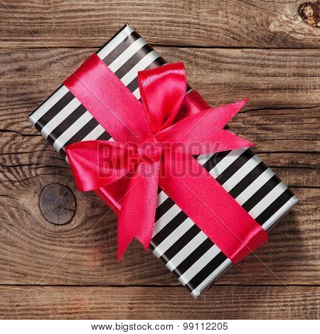 Fashionable Striped Gift Box With A Pink Bow On Board.