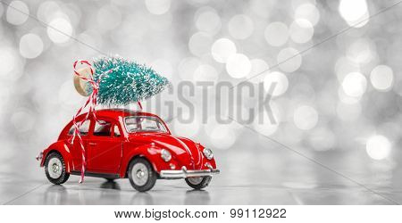 Miniature red car with fir tree on abstract background