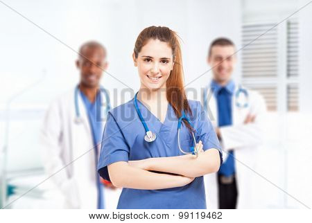 Young smiling nurse in front of her medical team