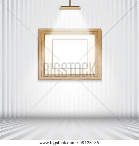 Spotlit room with empty wooden picture frame