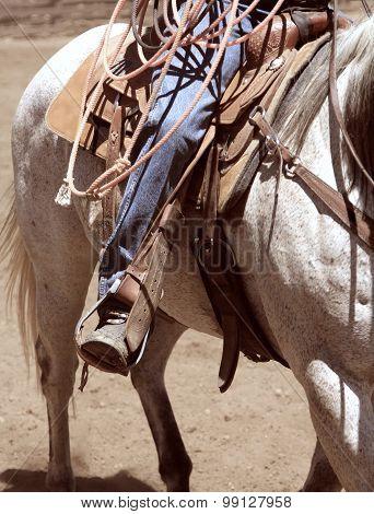 A cowboy riding his horse.
