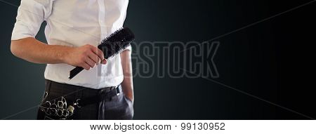 beauty and hair salon, hairstyle and people concept - close up of male stylist with brush at salon over blank black background