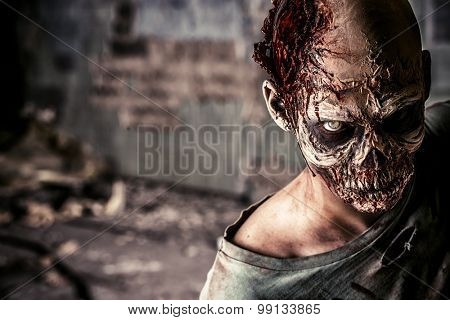 Horrible scary zombie man on the ruins of an old house. Horror. Halloween.