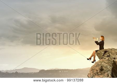 Young businesswoman sitting on rock edge and proclaiming something in horn